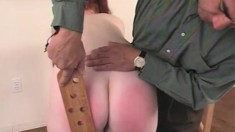 Redhead Is Bent Over A Chair And He Whacks Her With A Paddle