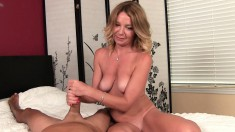 Busty blonde MILF Mrs. Summers strokes a thick cock in a two-fist handjob