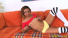 Brunette Latina is on the couch stripping and giving a good tease