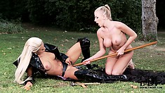 Busty mistress uses a stick to fuck her slave in the great outdoors