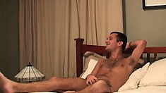 Horny young guy lies fully naked on the bed stroking his big shaft