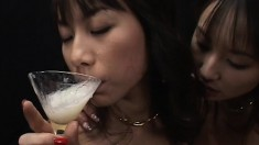 Two lusty Asian babes kiss with their mouths full of hot cum