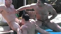 Three muscled studs show off their six-packs during a hot gay three-way in the pool