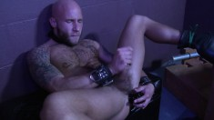 Tattooed stud jerks on his pecker and shoves a dildo up his ass