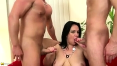 Sexy busty brunette sucks two cock in group sex